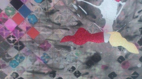 Auf einem grauen Hintergrund sind bunte Quadrate sowie ein roter und ein gelber glitzernder Umriss.